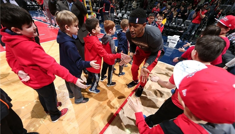 Bradley Beal high-fives a group of young fans as he enters the court
