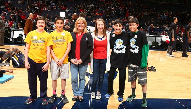 Women and children standing mid-court at Capital One Arena before a game