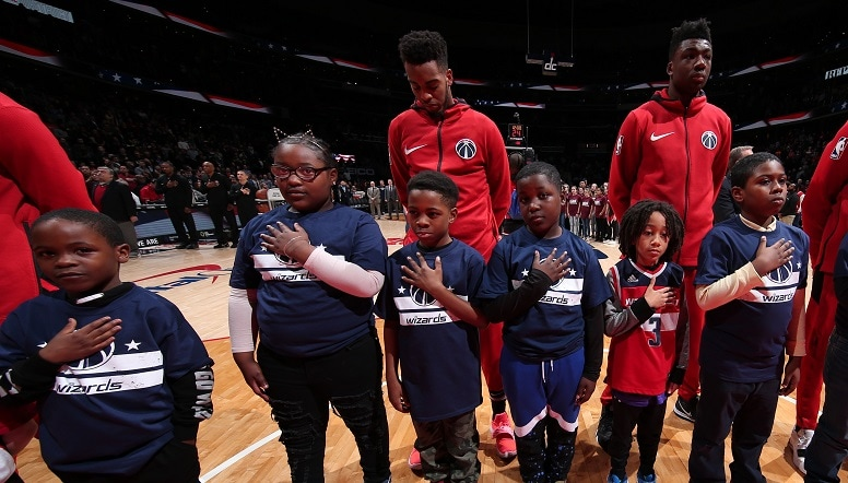 Troy Brown Jr. and Thomas Bryant stand for the National Anthem with a group of children
