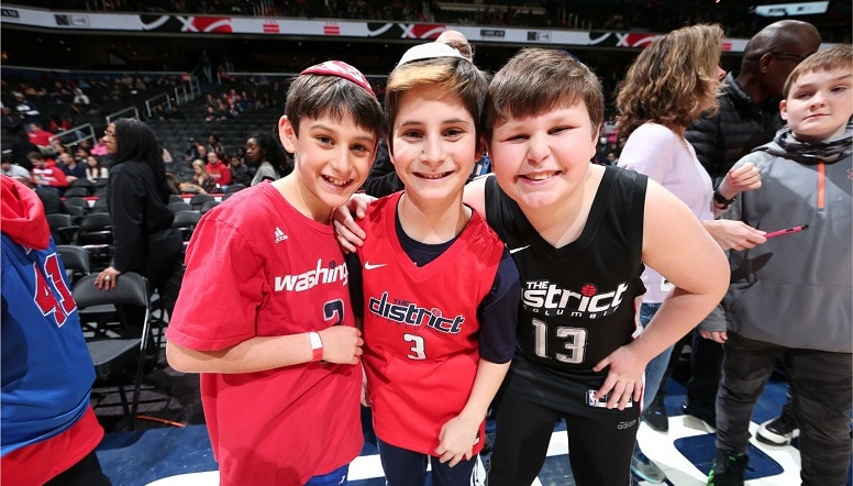 Three boys pose for a picture mid-court after a Wizards game