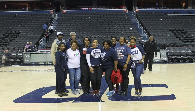 A group of men and women pose for a photo mid-court at Capital One Arena